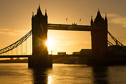 © Licensed to London News Pictures. 26/11/2017. London, UK. A bus travels across Tower Bridge on the River Thames at sunrise this morning during cold and clear weather. Photo credit: Vickie Flores/LNP