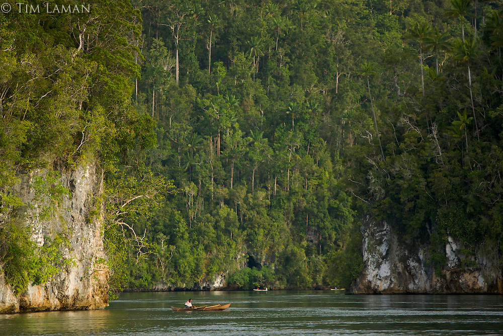 Fisherman in canoes  are dwarfed by the landscape of Mayalibit Bay.  This cliff lined passage is the narrow entrance to the huge bay.