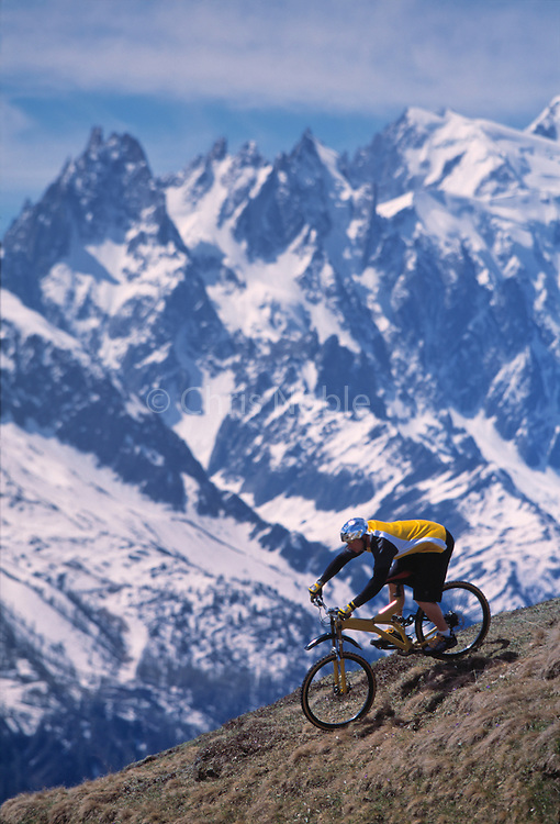 A male mountain biker descends a slope before the Aiguilles of Chamonix in the French Alps near Chamonix France.
