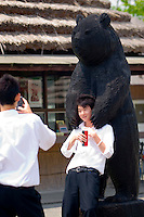 A young boy poses for a photograph while being 'mauled' by a wooden bear.