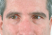 close up of a middle aged man's face with his eyes looking to the left