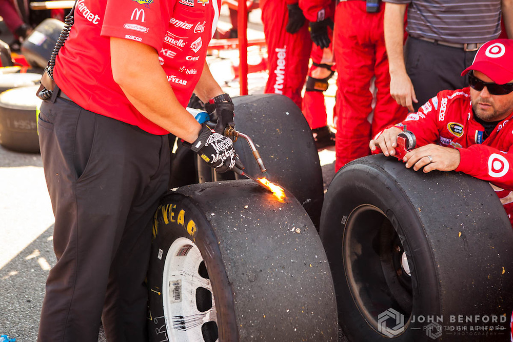 A driver's pit crew member uses a blowtorch and _____ to clear away debris from the wear holes on a set of used tires, while a fellow crew member measures the depth of the wear holes on another tire during the NH 301 NASCAR Sprint Cup race at New Hampshire Motor Speedway.