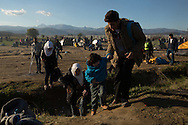 A syrian family crosses a ditch while walking toward the border crossing on December 3, 2015 after hearing a rumor that the border to Macedonia may be reopened soon, after it was blocked by a group of protestors the day before.