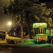 A rickshaw-walla (a rickshaw driver) stoped for ice cream on the side of the road at night in New Delhi. Ice cream vendors like this one will stay up all night during the summer waiting for a car to pull over and buy an ocasional ice ceram cone.