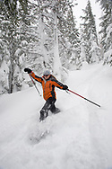 Low angle view of a young woman in snowshoes with ski poles running down a snowshoe trail in deep powder in Bend, Oregon. (releasecode: jk_mr1033) (Model Released)