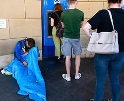 Homeless man sitting next to queue of public using ATM cash dispensing machine on the Royal Mile in Edinburgh, Scotland, UK