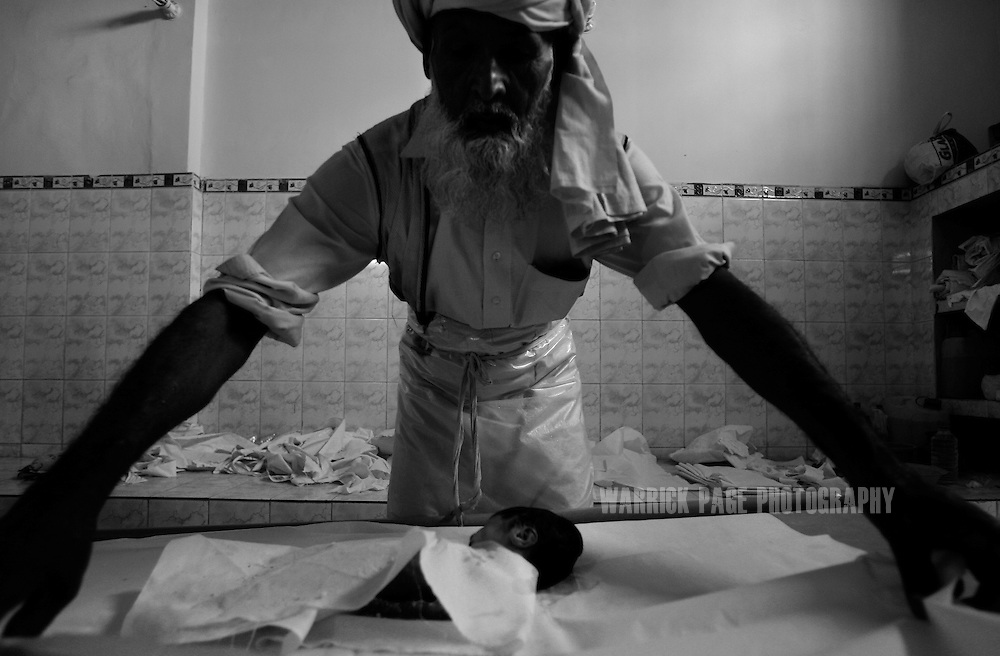 KARACHI, PAKISTAN - APRIL 18: A mortuary worker wraps an abandoned newborn baby in a burial shroud in accordance with Islamic tradition at the Edhi Morgue on April 18, 2008 in Karachi, Pakistan. The Edhi Foundation urges women give up unwanted children rather than abandon or kill in order to cover up children conceived out of wedlock, or through rape. The Edhi Foundation orphanages represent a microcosm of Pakistan's absolute poverty where children are its first casualty, tragedy and hope collide on a daily basis, and life and death are in constant flux existing only rooms apart. Pakistan is a country more than a third of it's population live in absolute poverty. As world attention fixates on Pakistan's ongoing political turmoil, generations of children are being abandoned due to Pakistan's spiraling poverty and growing instability. Some are born out of wedlock - a major social taboo - others discarded due to physical and mental disabilities, but nearly all are abandoned due to poverty. Boys and girls alike are abandoned every year, found in dumpsters mauled by rats and dogs, or left to fend for themselves on the streets of Karachi's sprawling and unforgiving metropolis. The lucky ones find their way to the Edhi Foundation orphanages. (Photo by Warrick Page)