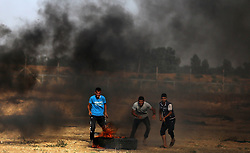June 9, 2017 - Gaza City, Gaza Strip, Palestinian Territory - Palestinian protesters take cover during clashes with Israeli security forces following a demonstration against the blockade on the Gaza Strip, near the border fence east of Jabalia refugee camp on June 9, 2017  (Credit Image: © Yasser Qudih/APA Images via ZUMA Wire)