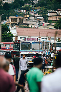 Intercity buses make their way through a small market in downtown Kandy, Sri Lanka, Asia