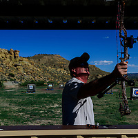 Dave Miller puts his bow on rack before going to the range to pick up his arrows on Thursday at the Gallup Bow Club in Gallup. The club meets every Thursday.