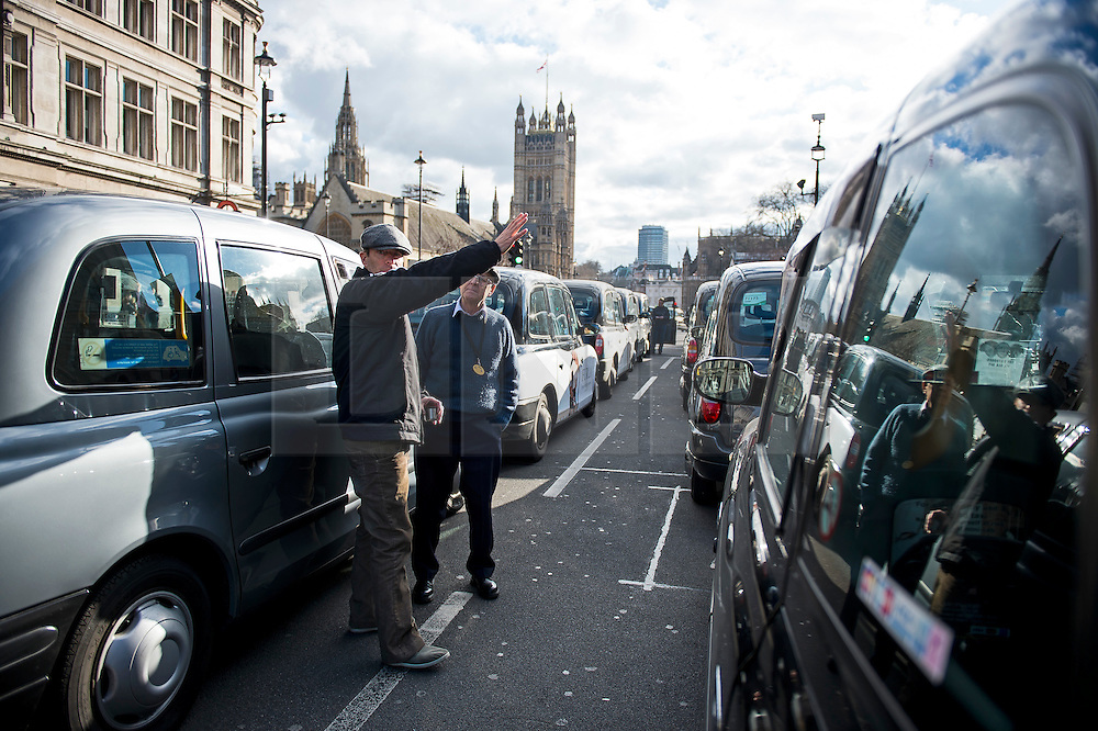 © Licensed to London News Pictures. 10/02/2016. London, UK. Thousands of London black cab drivers stage a protest in Westminster, London against Government interference in the taxi industry and 'active support' for Uber, which they allege is a 'tax avoiding global corporation' Photo credit: Ben Cawthra/LNP