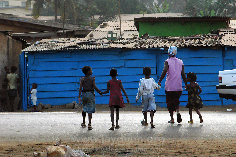 GHANA,Accra,Kokomlemle, 2007. Children get some help crossing a busy street across from the railroad tracks. Accidents involving cars are all too common.