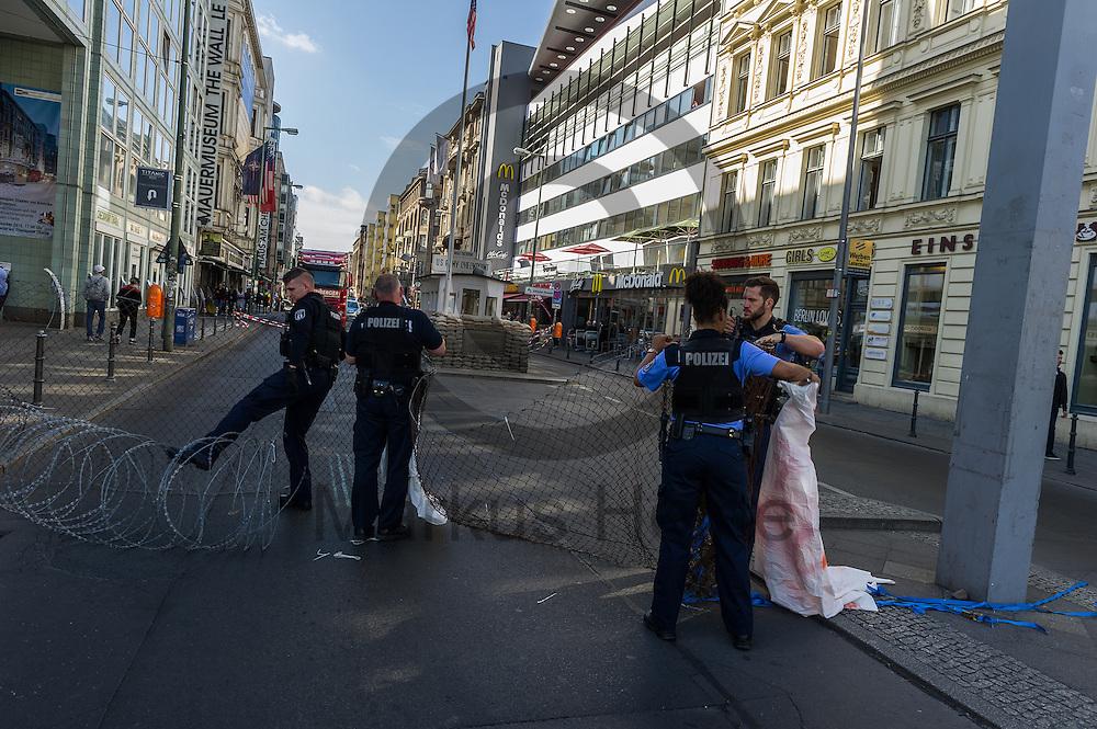 Polizisten bauen am 10.06.2016 an dem ehemaligen Grenz&uuml;bergang Checkpoint Charlie in Berlin, Deutschland einen symbolischen Grenzzaun ab. Die Aktivisten die die Aktion initiiert haben demonstrieren damit gegen die Abschottungspolitik der EU und die geschlossenen Grenzen. Foto: Markus Heine / heineimaging<br /> <br /> ------------------------------<br /> <br /> Ver&ouml;ffentlichung nur mit Fotografennennung, sowie gegen Honorar und Belegexemplar.<br /> <br /> Bankverbindung:<br /> IBAN: DE65660908000004437497<br /> BIC CODE: GENODE61BBB<br /> Badische Beamten Bank Karlsruhe<br /> <br /> USt-IdNr: DE291853306<br /> <br /> Please note:<br /> All rights reserved! Don't publish without copyright!<br /> <br /> Stand: 06.2016<br /> <br /> ------------------------------Aktivisten bauen am 10.06.2016 an dem ehemaligen Grenz&uuml;bergang Checkpoint Charlie in Berlin, Deutschland einen symbolischen Grenzzaun auf. Die Aktivisten demonstrieren mit der Aktion gegen die Abschottungspolitik der EU  und die geschlossenen Grenzen. Foto: Markus Heine / heineimaging<br /> <br /> ------------------------------<br /> <br /> Ver&ouml;ffentlichung nur mit Fotografennennung, sowie gegen Honorar und Belegexemplar.<br /> <br /> Bankverbindung:<br /> IBAN: DE65660908000004437497<br /> BIC CODE: GENODE61BBB<br /> Badische Beamten Bank Karlsruhe<br /> <br /> USt-IdNr: DE291853306<br /> <br /> Please note:<br /> All rights reserved! Don't publish without copyright!<br /> <br /> Stand: 06.2016<br /> <br /> ------------------------------