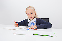Little girl drawing on paper at table