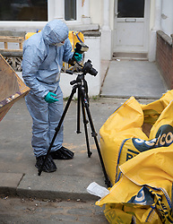 © Licensed to London News Pictures.19/03/2017.London, UK. A forensics officer photographs a builder's bag of sand which contains a hammer - found round the corner from a property on Wilberforce Road where one baby has been found dead and another seriously injured in Finsbury Park. Police have named  Bidhya Sagar Das who lives at the property and is wanted in connection with the death.  Photo credit: Peter Macdiarmid/LNP