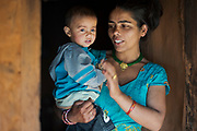 Srijana Phuyal and her 18 month-old daughter, Riya in the doorway of their home