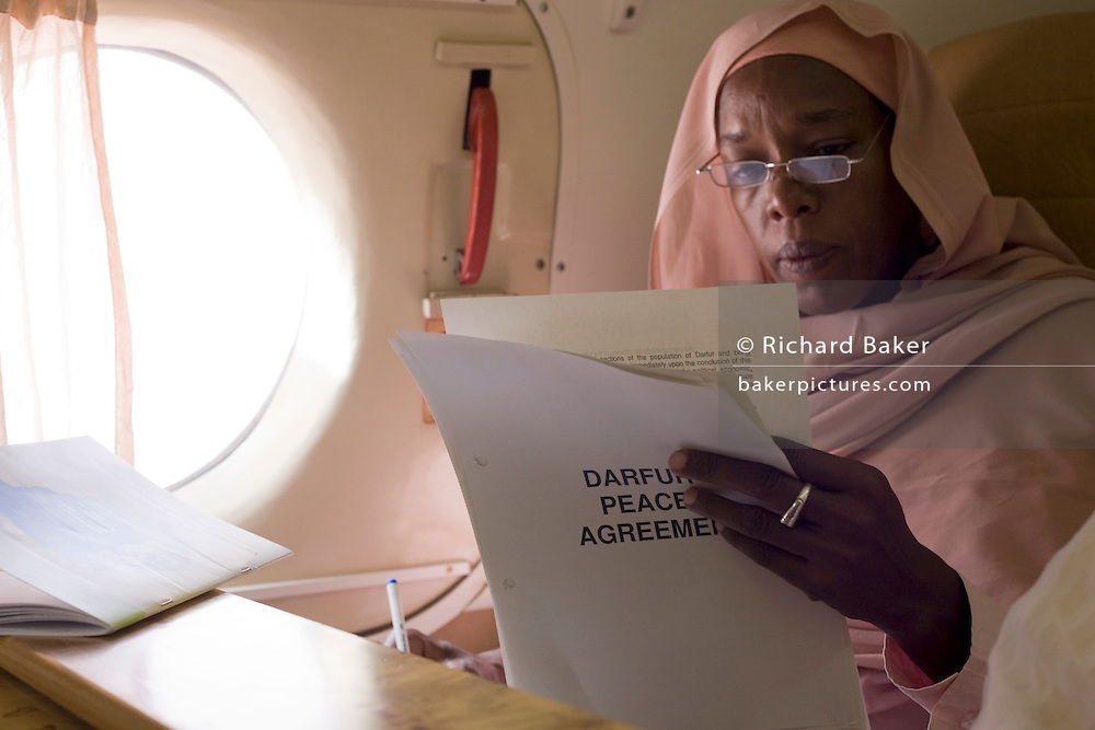 Dr Safaa Elagib Adam reads documents on the journey by air to the firstever international Conference on Womens' Challenge in Darfur. Seated in a chartered Russian Antonov aircraft during flight to Al Fasher (also spelled, Al-Fashir) where women from remote parts of Sudan gathered to discuss peace and political issues. The short flight saves her a hazardous five-day drive by road, known for extreme acts of violence by rebels and Janjaweed soldiers.