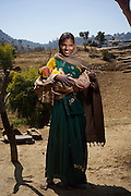 10th February 2012, Nalla Bada Village, Rajasthan, India. Mother of three Sudari Gorna (23, from the Gameti tribe) with her baby girl Krishna. Sudarna had PPH in December 2011 and was saved by application of a NASG (Non Pneumatic Anti-Shock Garment by ASHA (Accredited Social Health Activist) Basu Devi (34) <br /> <br /> RAKSHA (meaning 'protection' in Hindi) is Pathfinder's Post Partum Haemorrhage (PPH) intervention initiative. One critical aspect is the invention and use of the NASG (Non Pneumatic Anti-Shock Garment) to manage Hypovolemic Shock<br /> <br /> PHOTOGRAPH BY AND COPYRIGHT OF SIMON DE TREY-WHITE<br /> <br /> + 91 98103 99809<br /> + 91 11 435 06980<br /> +44 07966 405896<br /> +44 1963 220 745<br /> email: simon@simondetreywhite.com photographer in delhi