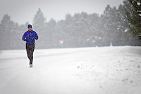 Don Witulski jogs along Coeur d'Alene Lake Drive during a snow storm Tuesday.