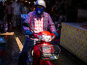 "03 APRIL 2014 - BANGKOK, THAILAND:  A man rides a motorcycle through Khlong Toey Market in Bangkok. Khlong Toey (also called Khlong Toei) Market is one of the largest ""wet markets"" in Thailand. The market is located in the midst of one of Bangkok's largest slum areas and close to the city's original deep water port. Thousands of people live in the neighboring slum area. Thousands more shop in the sprawling market for fresh fruits and vegetables as well meat, fish and poultry.     PHOTO BY JACK KURTZ"