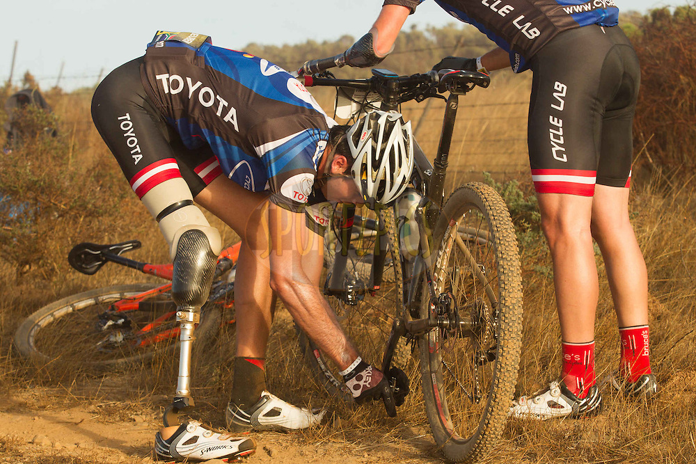 Reuben Van Niekerk helps fellow amputee and team-mate Dane Wilson with  a technical problem during the Prologue of the 2013 Absa Cape Epic Mountain Bike stage race held at Meerendal Wine Estate in Durbanville outside Cape Town, South Africa on the 17 March 2013..Photo by Greg Beadle/Cape Epic/SPORTZPICS