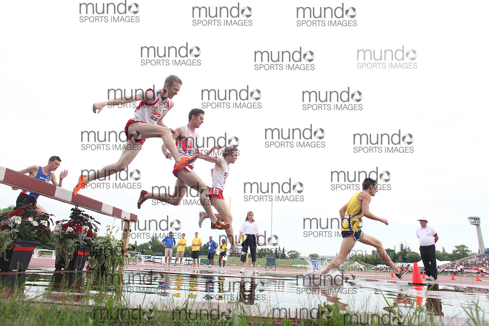 Winnipeg, Manitoba ---11-07-08--- Competitors traverse the water barrier in the mens steeplechase at the 2011 Canadian Junior National Track and Field Championships in Winnipeg, Manitoba,  July 08, 2011..GEOFF ROBINS/ Mundo Sport Images.