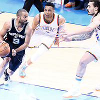 08 May 2016: San Antonio Spurs guard Tony Parker (9) drives past Oklahoma City Thunder guard Russell Westbrook (0) and Oklahoma City Thunder center Steven Adams (12) during the Oklahoma City Thunder 111-97 victory over the San Antonio Spurs, during Game Four of the Western Conference Semifinals of the NBA Playoffs at the Chesapeake Energy Arena, Oklahoma City, Oklahoma, USA.