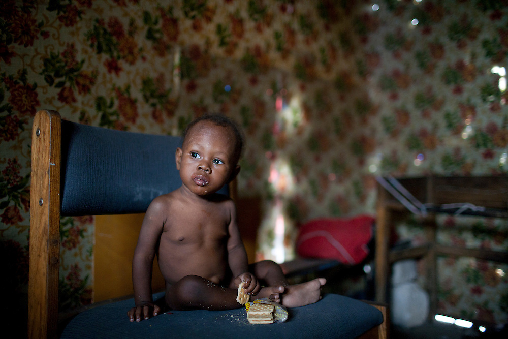A baby eats crackers in a tent in a camp for people displaced by the earthquake on Champs de Mars on July 14, 2010 in Port-au-Prince, Haiti.