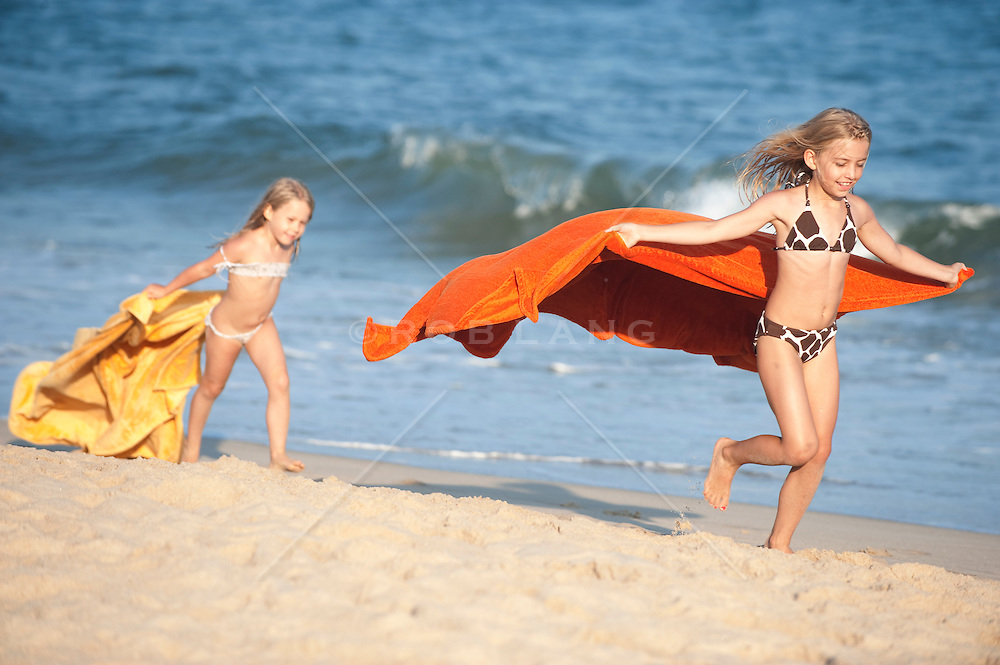 two little girls running and playing on the beach