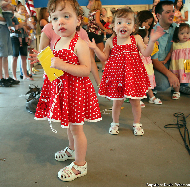 ALIKE BUT DIFFERENT - Sidney Swartzendruber, right, seems a little more excited about the Twins, Triplets and More Contest than identical sister Addison, as they take the stage at the Wellmark Blue Cross Blue Shield Stage at the fairgrounds in Des Moines, Iowa, in 2007.
