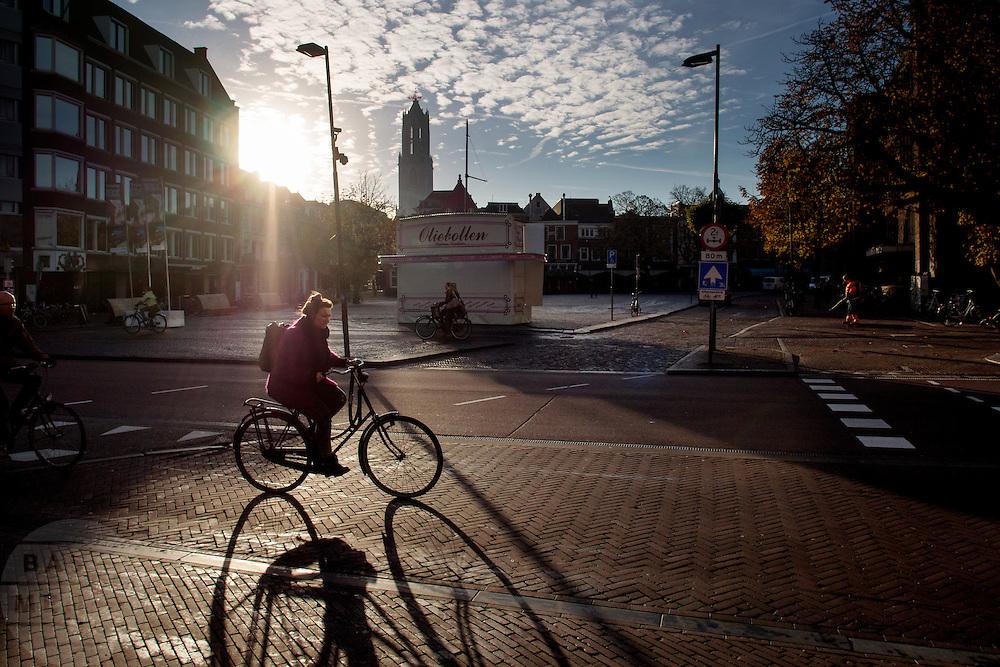 In Utrecht rijden fietsers in een mooie herfstzon over de Neude in Utrecht.<br /> <br /> In Utrecht cyclists are riding at the Neude.