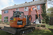 Crane and workmen removing Aga cooker from house about to be demolished, Shottisham, Suffolk, England