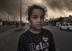 November 2, 2016 - Al Qayyarah, Nineveh Governorate, Iraq - A local girl in the smoke of burning oil at Al Qayyarah. ISIS militants set fire to a large sulfur plant and oil fields in the area. (Credit Image: © Bertalan Feher via ZUMA Wire)