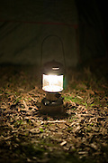 lantern glowing sitting on the ground while camping