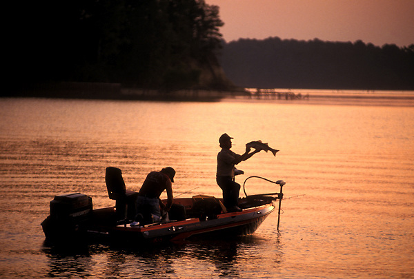 Sunset silhouette of two fishermen with a fresh caught fish in a boat on a lake.