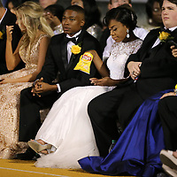 Tupelo Homecoming maid Jasman Mitchell has her hands full with a bag of chips and her cell phone as they wait for halftime.