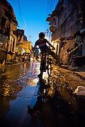A young boy teeter-totters past a broken sewage line that has submerged the street with raw sewage.