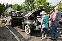 "Visitors read about Larry Young's 1961 Ford ""MNSHNR"" during Cruise Night at the Gilford Community Center Thursday evening.  (Karen Bobotas/for the Laconia Daily Sun)"