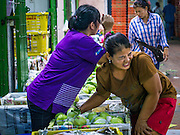 19 OCTOBER 2012 - BANGKOK, THAILAND:   A vendor gives her coworker a massage in their booth in the Bangkok Flower Market. The Bangkok Flower Market (Pak Klong Talad) is the biggest wholesale and retail fresh flower market in Bangkok.  The market is busiest between 3:30AM and 6AM. Thais grow and use a lot of flowers. Some, like marigolds and lotus, are used for religious purposes. Others are purely ornamental.         PHOTO BY JACK KURTZ