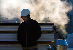 BRUSSELS, BELGIUM - APRIL-04-2007 -  A construction worker tries to keep warm while on a break. (Photo  © Jock Fistick)