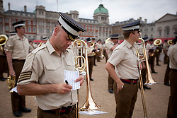 © Licensed to London News Pictures. 10/06/2013. London, UK. A bandsman of the Coldstream Guards writes notes on his sheet music as the Massed Bands of the British Army's Household Division carry out a dress rehearsal ahead of the annual Beating Retreat ceremony in London today (10/06/2013). The musical event, which takes place on Horse Guards Parade, will be held on the 12th and 13th of June this year, with Prince Philip and the Queen attending. Photo credit: Matt Cetti-Roberts. Photo credit: Matt Cetti-Roberts/LNP