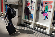 A traveller pulls his wheelie case behind him and passes a shop frontage featuring a bag-carrying shopper, in the City of London, the capital's financial district, on 10th May 2019, in London, England.