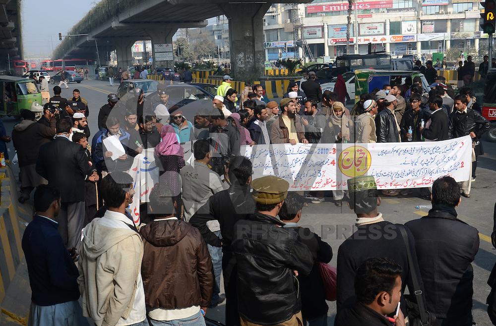 LAHORE, PAQUISTÃO, 12.01.2014: PROTESTO-PAQUISTÃO - Paquistaneses, com faixas e cartazes, bloqueiam estrada principal de ônibus e metrô, durante protesto contra o desemprego, em Lahore, nesta terça-feira. (Foto: Rana Sajid Hussain/Brazil Photo Press)