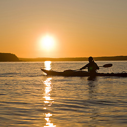 A woman sea kayaking near Sheep Porcupine Island in Maine's Acadia National Park.  Bar Harbor. Sunrise.