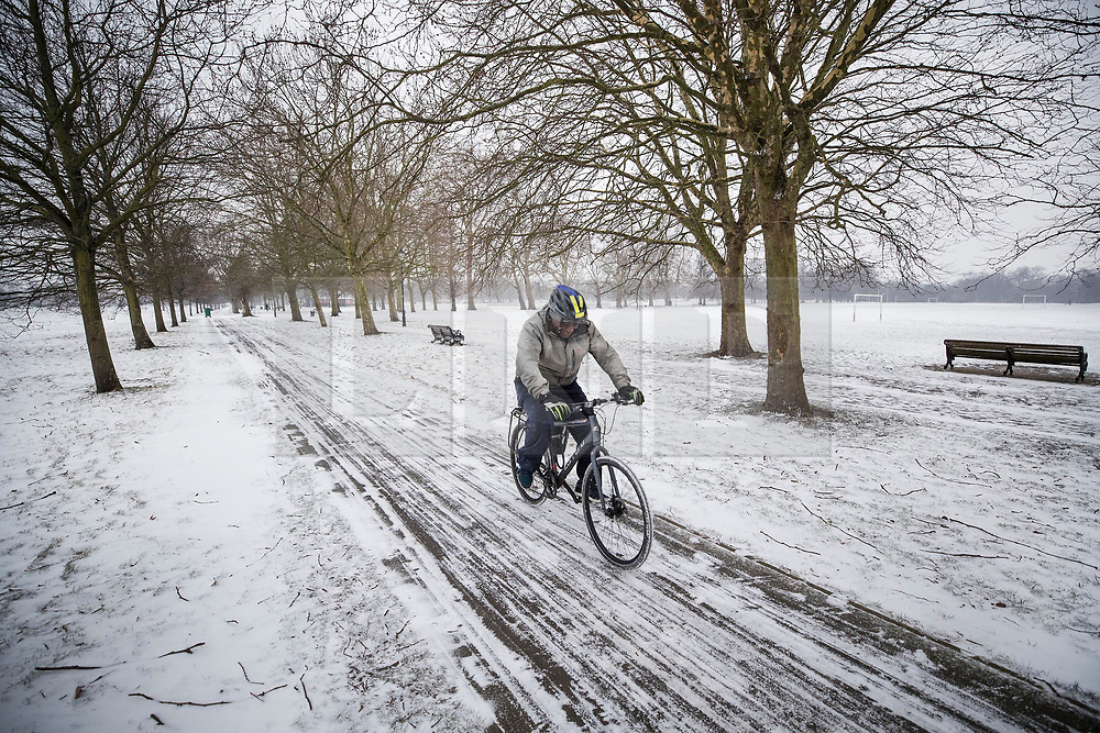 © Licensed to London News Pictures. 01/03/2018. London, UK. A cyclist makes his way to work on Clapham Common after more snow fell overnight. The 'Beast from the East' and Storm Emma have brought extreme cold and heavy snow to the UK. Photo credit: Peter Macdiarmid/LNP
