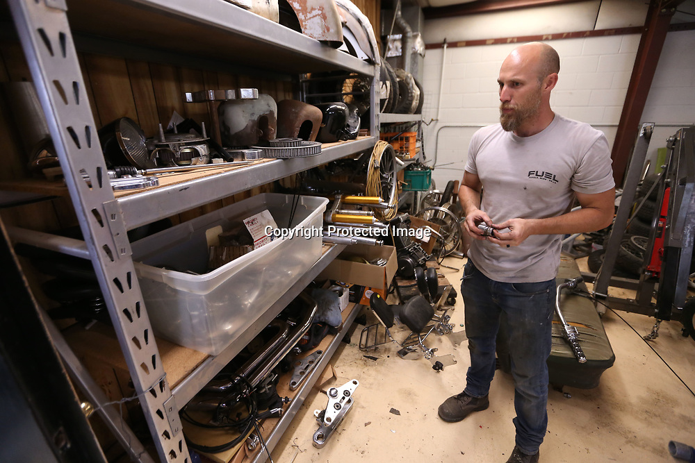 Kevin Doyle looks for a part to go on a motorcycle he's working on in his shop.
