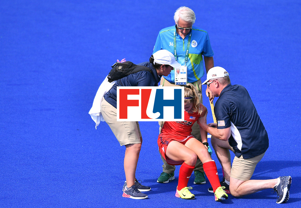 The USA's Katie Bam is helped to get up during the women's quarterfinal field hockey USA vs Germany match of the Rio 2016 Olympics Games at the Olympic Hockey Centre in Rio de Janeiro on August 15, 2016. / AFP / Carl DE SOUZA        (Photo credit should read CARL DE SOUZA/AFP/Getty Images)