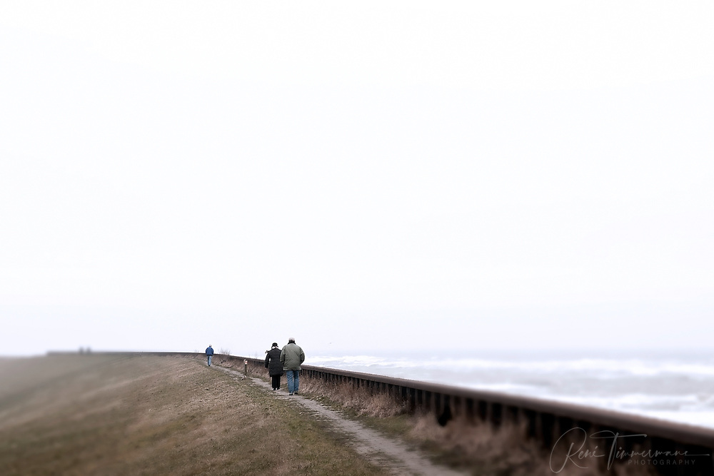 Walkers in stormy weather along the coastline of Petten in Noord Holland.