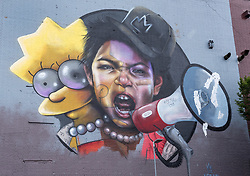 © Licensed to London News Pictures.  28/07/2018; Bristol, UK. Upfest, The Urban Paint Festival, 2018 with themes this year including the Simpsons cartoon series and 100 years of the first women getting the vote. NOMAD CLAN are pictured working on their giant mural with the character of Lisa Simpson on the side of the Tobacco Factory in Bedminster, Bristol. Nomad Clan is possibly the biggest female duo in world street art, having completed the largest mural in the country back in 2017. Their challenge this year is a unique one; to celebrate the suffrage movement with a tie in to The Simpsons using the show's titular post-modern feminist, Lisa Simpson. Upfest which is Europe's largest Street Art and Graffiti Festival takes place in the Bedminster area of Bristol between Saturday the 28th and Monday 30th of July. In celebration of their 10th anniversary, Upfest will feature the animated family, The Simpsons with 2018 festival goers treated to artist interpretations including Homer, Marge, Bart, Lisa, and Maggie. The festival has also teamed up with Bristol Women's Voice to celebrate the centenary of the first votes for women, and together Upfest and Bristol Women's Voice will celebrate the progress made since 1918, with three artists including Nomad Clan chosen to portray the suffrage movement and the rights of women. Upfest will have 400 artists from 70 countries in attendance, including this year's lead artists Insane51, L7m, London Police, Nomad Clan, Odeith, and Paris. This year, three Upfest artists have been selected by The Simpsons creator Matt Groening to bring The Simpsons to life in their own unique styles: Bao, born and based in Hong Kong, is known for her freestyle work with vibrant murals and illustrations; Soker, a wildstyle writer, is one of Bristol's finest talents and has been putting his mark on the city since the late 80's; Nomad Clan, the collective of Cbloxx and AYLO, one of the most sought-after duos in the international global street art scene.