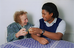 Carer sitting at table with elderly woman laughing and toasting glasses,